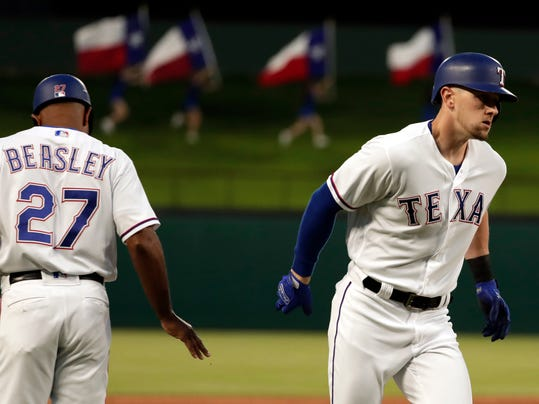 Texas Rangers third base coach Tony Beasley (27) congratulates Ryan Rua, right, on his solo home run in the third inning of a baseball game against the Los Angeles Angels in Arlington, Texas, Wednesday April 11, 2018. (AP Photo/Tony Gutierrez)