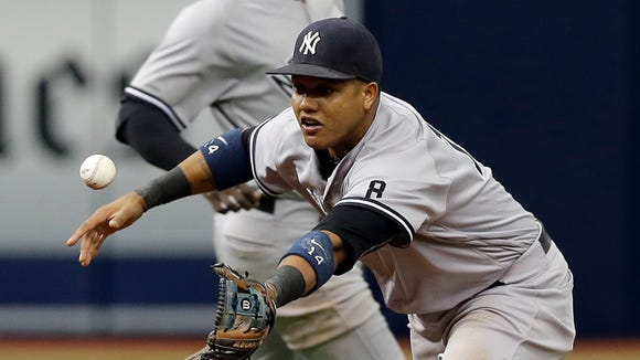 New York Yankees second baseman Starlin Castro makes an error on a ground ball hit by Tampa Bay Rays' Curt Casali during the fifth inning of a baseball game Sunday, May 29, 2016, in St. Petersburg, Fla.  Yankees' Didi Gregorius backs up the play.