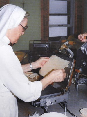 The late Sr. Lelia Leisgang of the Salvatorian Sisters is shown making a few of the millions of hosts made each year in St. Nazianz, in this 1941 photo.