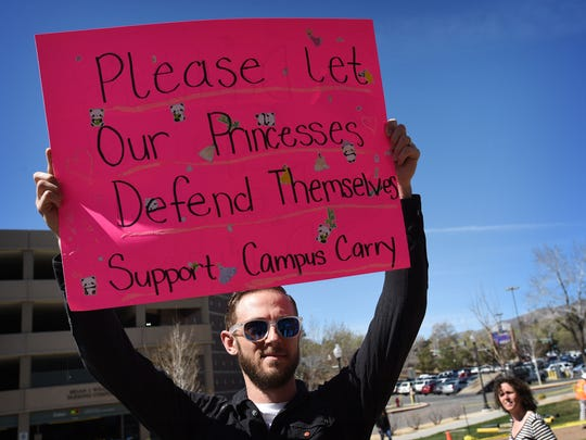 "UNR alum Sam England holds a sign in favor of allowing guns on campus during a planned protest against the ""campus carry"" bill at the University of Nevada in Reno on March 25, 2015."