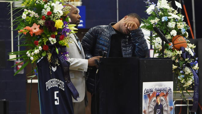 Akili Hill, 17, right, a student at Poughkeepsie High School and a member of the school's boys varsity basketball team, is overcome with emotion during the memorial service for former teammate Caval Haylett Jr., who was shot on March 9, 2016. Assistant Principal Da'Ron Wilson, left, stands by with a microphone.