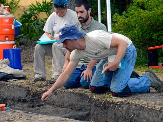 University of West Florida archaeology student Mark Roberson shaves layers of soil at one of the Luna excavation sites as supervisor Michael DuBose looks on. Archaeology student Lindsey Howell-Franklin records her findings.