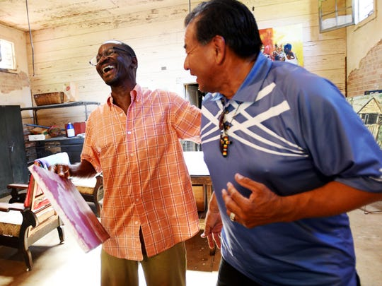 Ray Stevenson, left, and artist Elmer Yazzie share a laugh during their recent visit to look at the art from the Chinle Boarding School students.