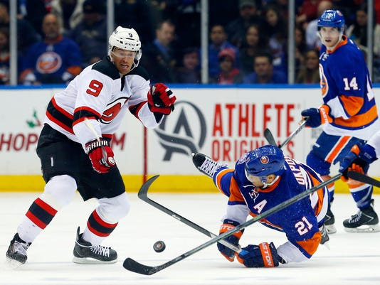 Martin Havlat (9) of the New Jersey Devils collides with New York Islanders Kyle Okposo (21) in the third period of the NHL hockey game at Nassau Coliseum on Monday, Dec. 15, 2014 in Uniondale, N.Y.  (AP Photo/Newsday, Jim McIsaac)  NYC LOCALS OUT By Jim McIsaac NY OUT
