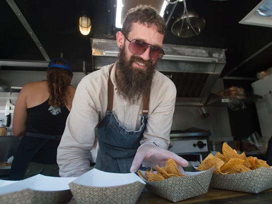 Tim Meador plates up a line of nachos at Tramp About while the truck serves the brewery crowd at New Belgium Brewing on Friday, July 13, 2018.