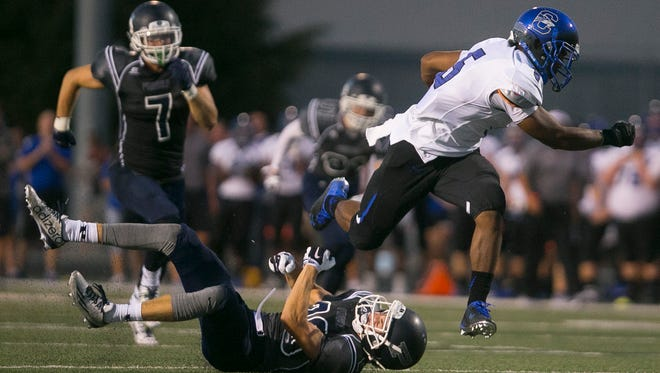 Chandler's Kolby Taylor (5) breaks a tackle from Pinnacle's Nick Spohn on his way to the end zone for a touchdown at Pinnacle High School in Phoenix, AZ on August 20, 2015.