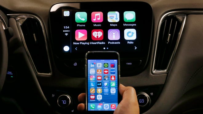 An iPhone is connected to a 2016 Chevrolet Malibu equipped with Apple CarPlay apps, displayed on the car's MyLink screen during a demonstration in Detroit on Tuesday.
