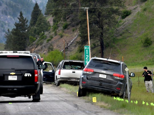Law enforcement personnel investigate the scene of a shootout on Interstate 90 east of Missoula following a high-speed chase Tuesday. The white SUV was the vehicle being pursued. The driver of the SUV has been arrested and a passenger was shot by law enforcement and taken to the hospital.