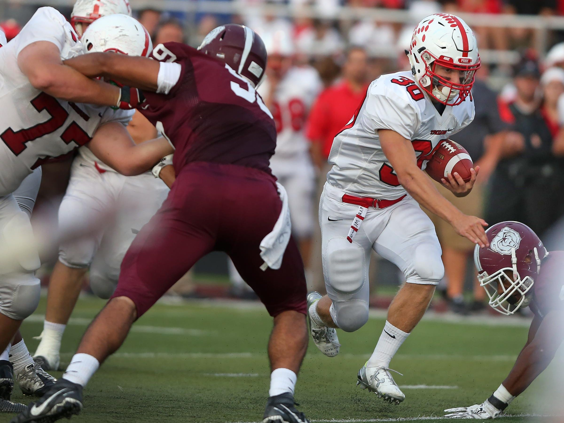 Center Grove #30 Titus McCoy dances through a hole for yardage in first half action during the Center Grove at Lawrence Central football game, Friday, September 25, 2015. Center Grove won 44-26.