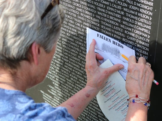 Helen Myerholtz, of Gibsonburg, looks for her brother's name, Glen Millenger, of Oak Harbor, who died in the Vietnam War.