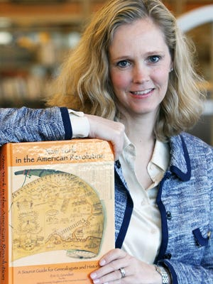 Kari Weis with a Daughters of the American Revolution genealogy book at the Chappaqua Public Library Nov 17, 2015.