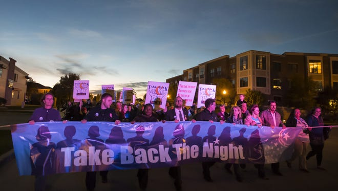 Dignitaries lead the Take Back The Night march Wednesday, Oct. 7, 2015, on the streets of Oshkosh.