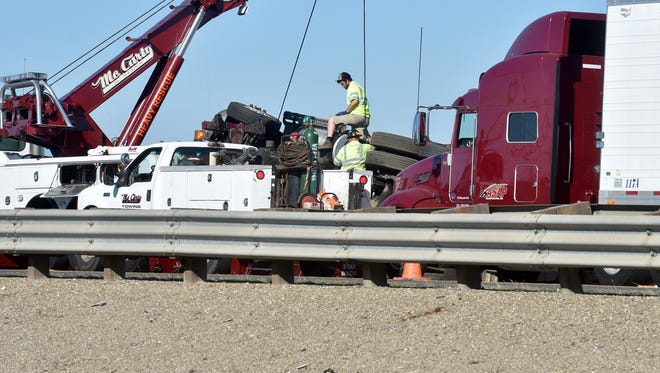 Workers try to raise an overturned semi-tractor Thursday on Highway 101.