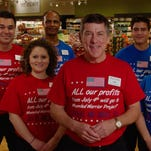 Ian McLeod, CEO and president of Southeastern Grocers, center, poses with other team members. All proceeds Saturday at Winn-Dixie stores will be donated to the Wounded Warrior Project's Independence Program.