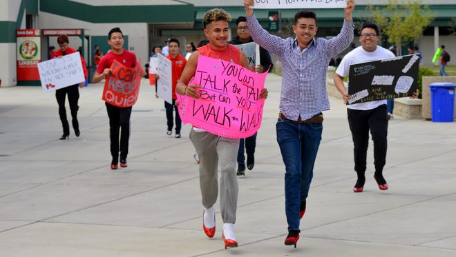 "Lindsay High School male students and faculty participate in the campus' ""Walk a Mile in Her Shoes"" event Tuesday afternoon.  The event it to help prevent sexual violence of women."