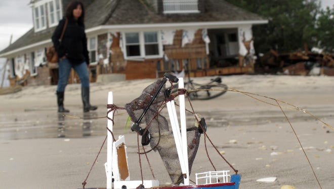 This Oct. 31, 2012 photo shows a woman walking on a beach in Mantoloking N.J. past a house destroyed by Superstorm Sandy.