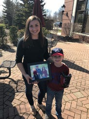 Family's all here as Allison Mankowski (left) and Dominik, 6, hold a framed photograph which includes 2-year-old Stella and Joshua Mankowski, deployed with the U.S. Coast Guard at Guantanamo Bay in Cuba until July.
