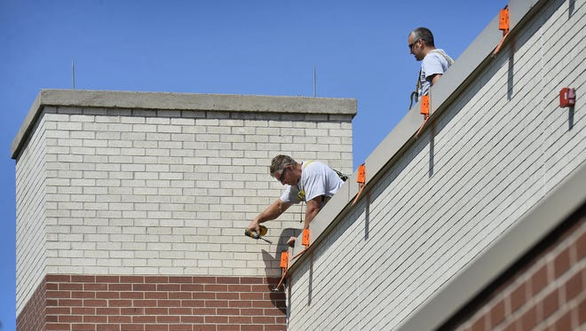 Roofers with McDowall Co., St. Cloud, set up safety equipment for a roofing job in August 2015 at Oak Hill Community School.