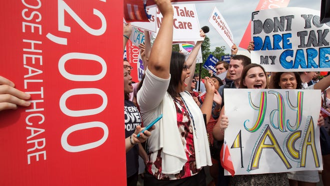 """Jessica Ellis, right, with """"yay 4 ACA"""" sign, and other supporters of the Affordable Care Act react with cheers as the opinion for health care is reported outside of the Supreme Court on Thursday."""