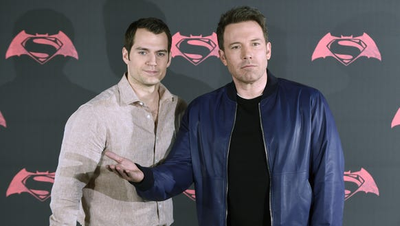 Affleck (R) and co-star Henry Cavill (L) pose for photographers