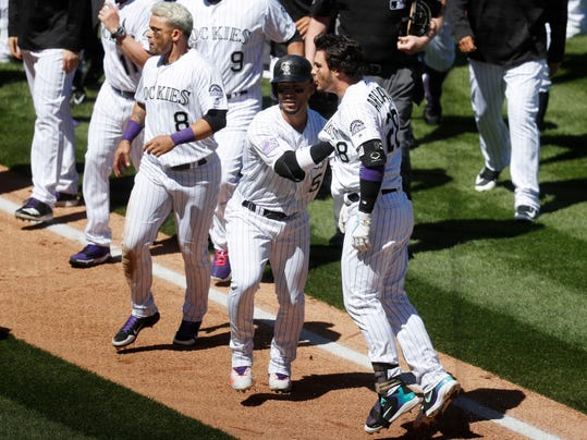 Colorado Rockies' Nolan Arenado, front right, is restrained by Carlos Gonzalez, center, as Gerrardo Parra, left, keeps an eye on the San Diego Padres dugout after Arenado rushed the mound following getting hit by a pitch from Padres starting pitcher Luis Perdomo in the third inning of a baseball game Wednesday, April 11, 2018, in Denver. (AP Photo/David Zalubowski)