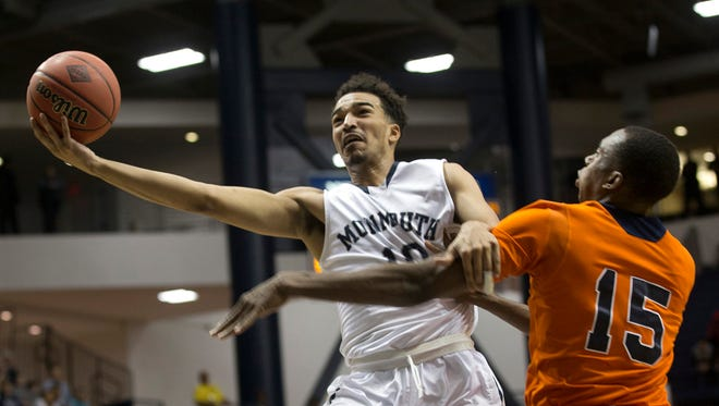 Monmouth's Micah Seaborn drive with a shot as Bucknell's Nate Jones tries to cover him. Monmouth University vs Bucknell in NIT first round game in West Long Branch, NJ on March 16, 2016.
