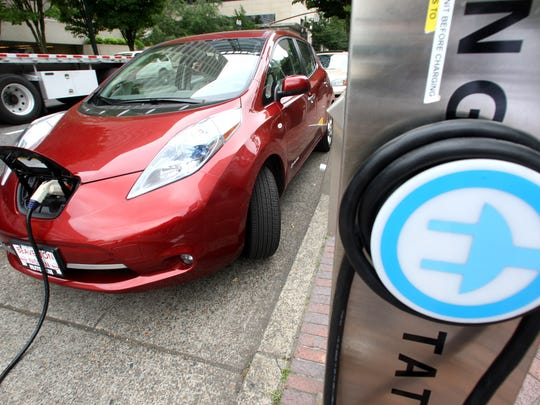 A Nissan Leaf charges at a electric vehicle charging station in Portland.