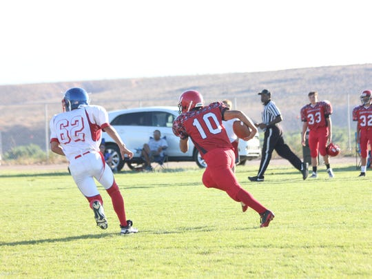 Beaver Dam's Uriel Perez runs past an Indian Springs player and heads for the end zone during a game last season.