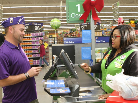 U.S. Army veteran Tom Sparr had the honor of being Walmart Neighborhood Market's first customer Wednesday morning. Whitney Fort handled the transaction for the former Fort Campbell soldier.