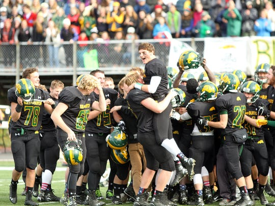 Burr and Burton quarterback Griffin Stalcup is lifted by a teammate after the Bulldogs' 28-7 win over Bellows Falls in the Division II state high school football championship game on Saturday, Nov. 7, 2015.