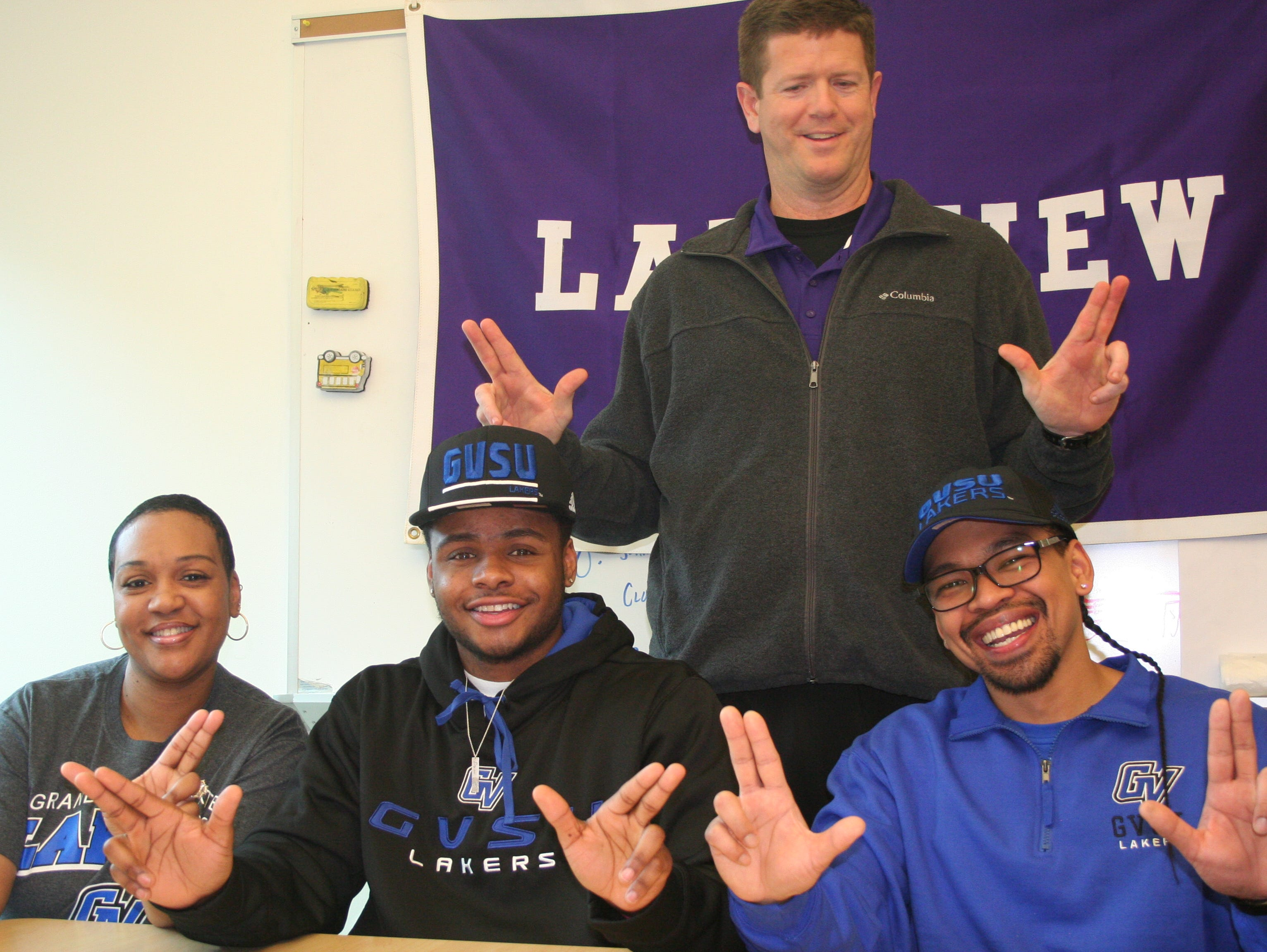 Lakeview's Dre'On Kemp shows the 'Anchor's Up' sign as he signs his National Letter of Intent to play football at Grand Valley State University. He is joined by his parents, Sakeeah Lewis-Galban and Jonathan Galban, along with Lakeview coach Matt Miller (standing).