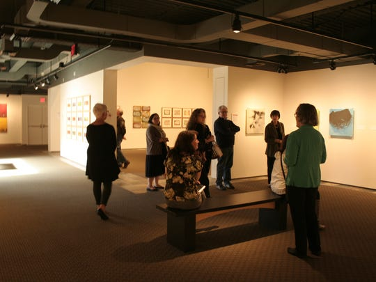 """Docent Janet Neuburg discusses the exhibit, """"James B. Thompson: Fragments of Time,"""" with visitors during the Gallery Talk at Hallie Ford Museum of Art on March 1."""