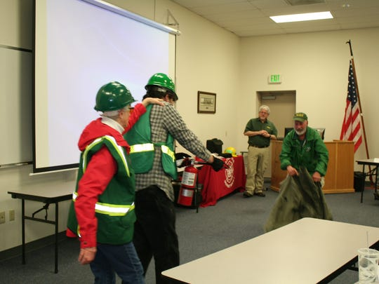 Coaches Lola Hackett (from left) and Ben Truitt team up to approach instructor Paul Guthrie, who is representing a fire, while instructor Terry Pickett looks on during the CERT training at Salem Fire Station #6 on March 10.