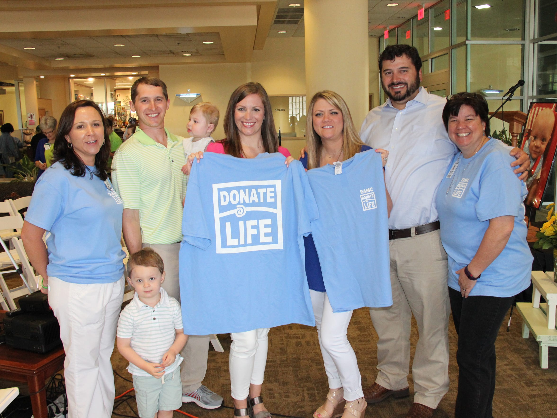 Lisa Harmon, nurse manager and chair of East Alabama Medical Center's Donate Life committee, Hudson Boswell, Tucker Boswell, Davis Boswell, Amanda Boswell, Holley Perry, Jonathan Perry and Laura Eason, EAMC chaplain, display Donate Life t-shirts following the hospital's annual Donate Life ceremony.