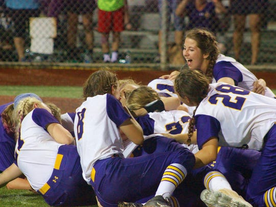 The ASH Lady Trojans have the dogpile following the Lady Trojans' Class 5A State championship victory over Zachary.