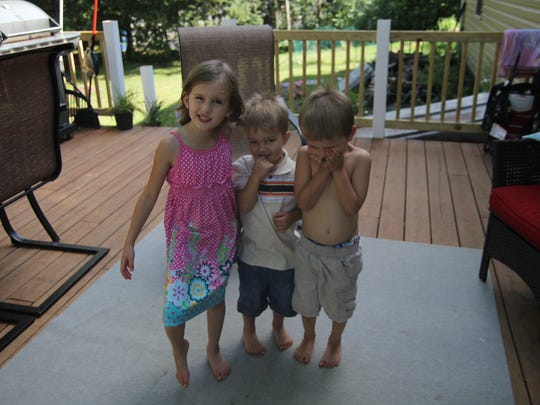 Jasmine, 6, Micah, 2 and Isaiah, 4, make faces on the back porch of their Wausau home.