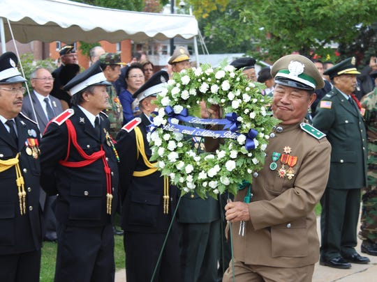 A Hmong-Lao military veteran carries a wreath to the base of the unveiled memorial Saturday, Sept. 24, 2016.