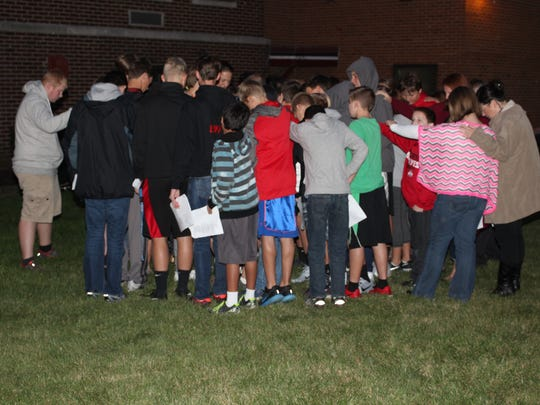 Pleasant middle and high school students form a tight circle for the closing prayer during See You at the Pole on Wednesday.