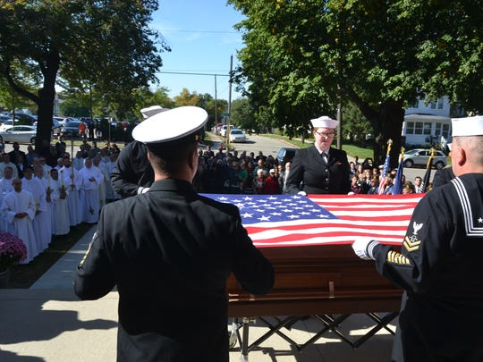 A Navy honor guard folds the flag that sat atop the Rev. Aloysius Schmitt's casket as a crowd of mourners watches. Schmitt was a Pearl Harbor hero whose remains were returned to Dubuque in October.