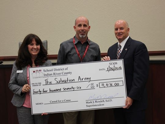 The Indian River County School District presents a donation to the 2015 Red Kettle campaign through the Casual for a Cause initiative. From left are School Board Chair Dale Simchick, John Corapi from the Salvation Army and Dr Rendell, school superintendent.