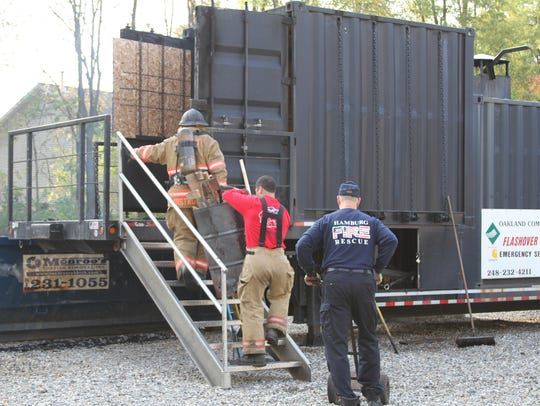 Firefighters load combustible material into a mobile