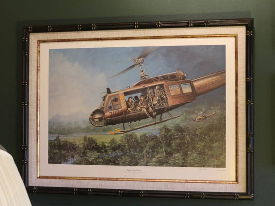 A picture of an Army helicopter on a mission hangs in the study of Bill Sawyer.