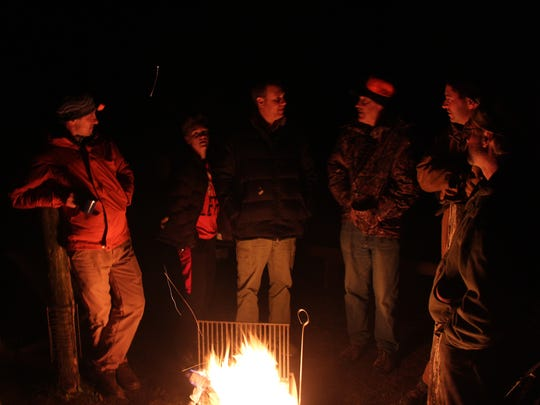 Hunters (from left) Jed Meunier of Madison, Isaac Watt of Dodgeville, Mike Watt of Dodgeville, Jim Wipperfurth of Sauk City, Brian Weigel of Sauk City and Steve Swenson of Baraboo talk around a campfire on the eve of the 2016 Wisconsin gun deer season.