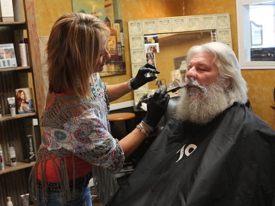 Cherri Miller trims Jim Elliott's beard.