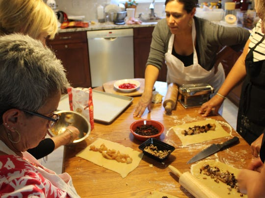 Angela Ranalli-Cicala guides friends and family members of Theresa Selover in Selover's Marlton home. The pastry chef grew up in the house and learned to cook in its kitchen.