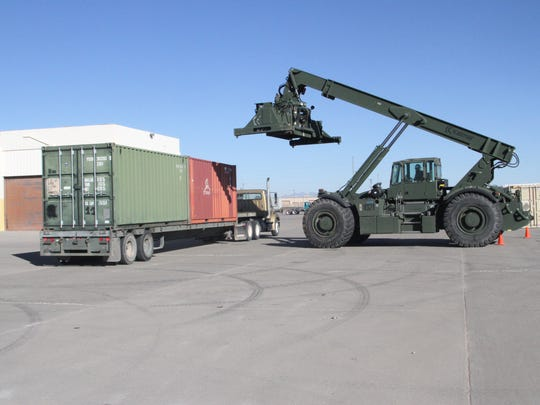 A civilian from the Defense Logistics Agency moves a container during Divestiture Week. The container was used to store sensitive items that were turned in.