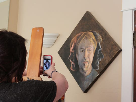 """Young artist Katelyn Ingram takes a photo of the """"Many Faces"""" of Art Slatten."""
