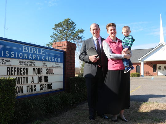 The Rev. Ben Lauritzen, his wife Kayla, and their son, Micah, in front of Bible Missionary Church.