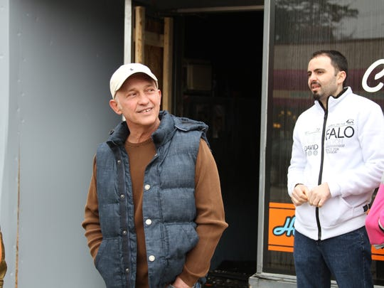 Mark's Midtown Coney owner Luigi Pecaj, left, talks with passers-by as restaurant employees watch outside his downtown Howell restaurant that burned Thursday night.