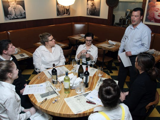 Employees at Cello talk about various wines during